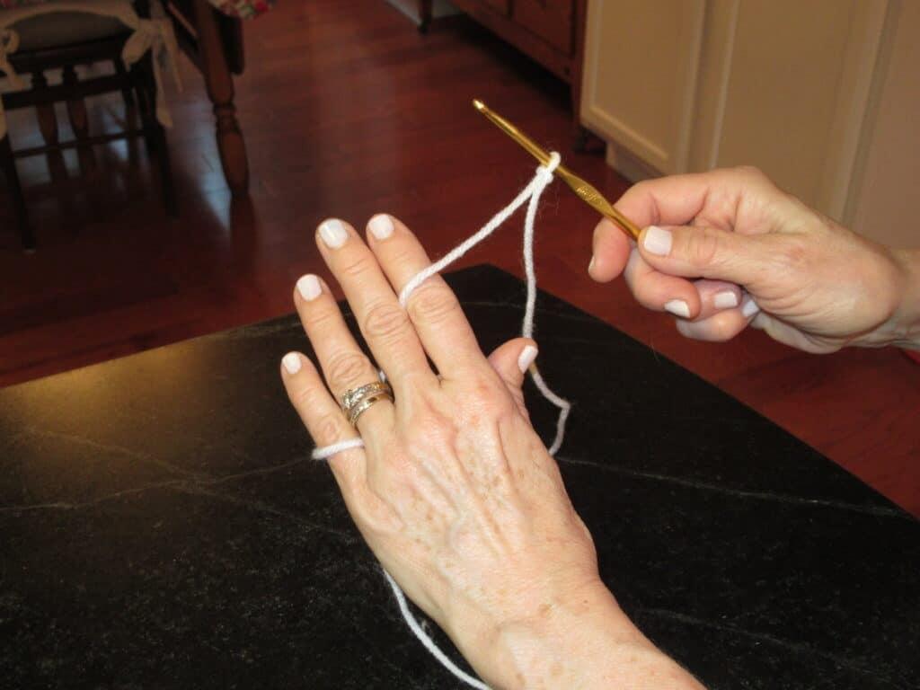 hands, white yarn, gold crochet hook