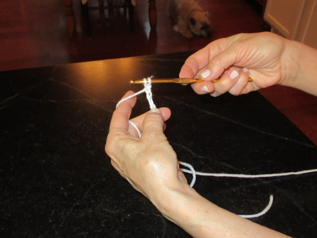 Two hands white yarn gold crochet hook