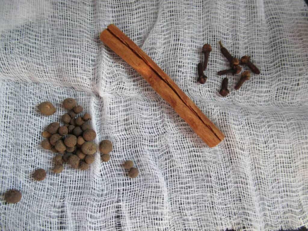 Allspice, cinnamon stick, cloves on cheesecloth