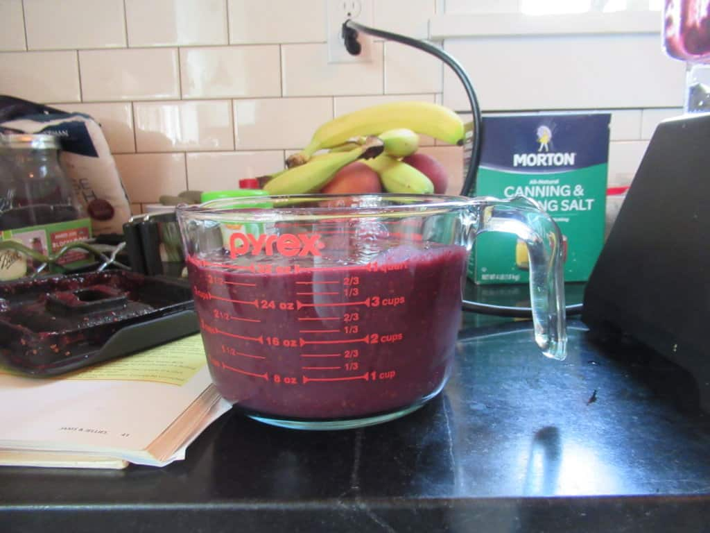 Blackberry puree in measuring cup on counter