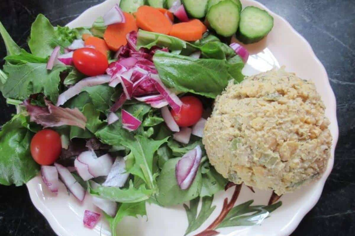 raw vegetables with a scoop of chickpea salad on a plate