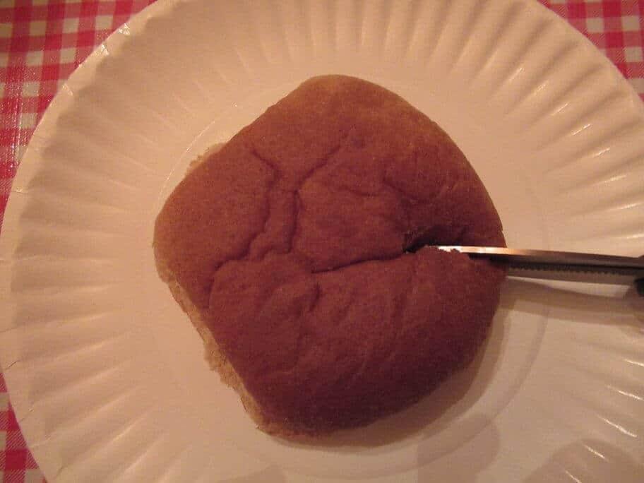 Cutting a hamburger bun with scissors