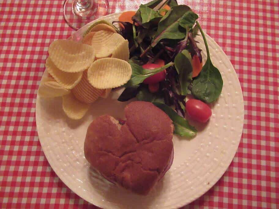 Heart-shaped Vegan Burger on bun with chips and salad