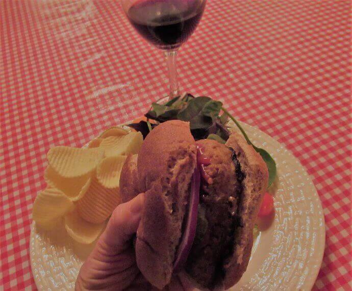Vegan burger on bun with chips salad and wine