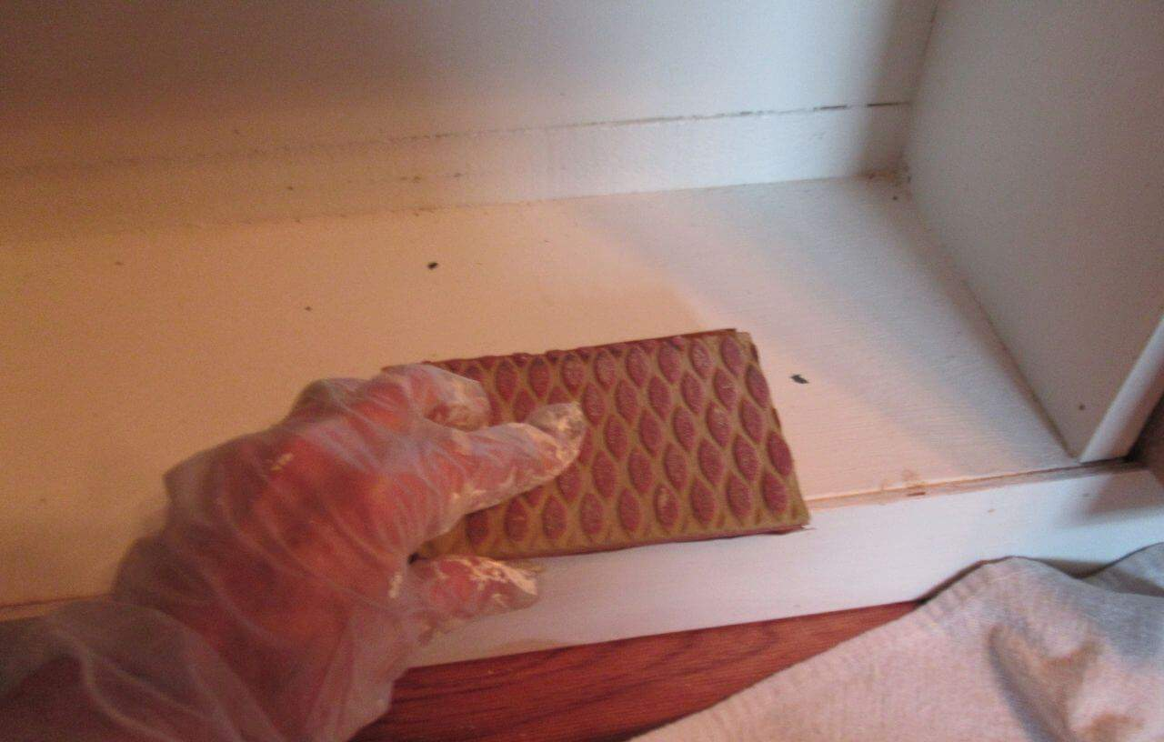 Sanding old painted wood with gloved hand