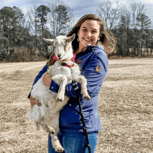 Smiling woman holding a goat