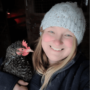 Smiling woman wearing hat holding chicken