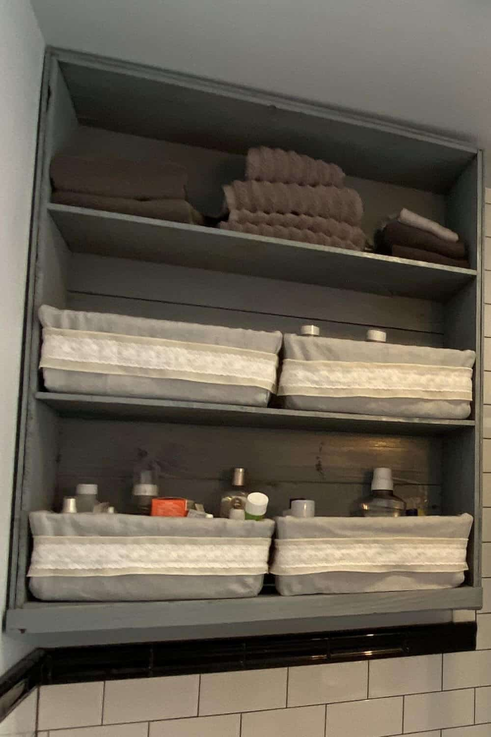 Gary bathroom shelves with towels and storage bins