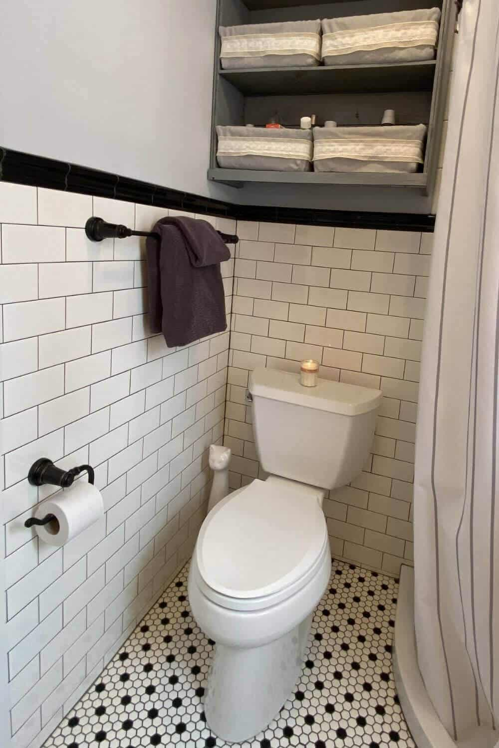 toilet, towel rack with towels, toilet paper holder, shelves, shower curtain