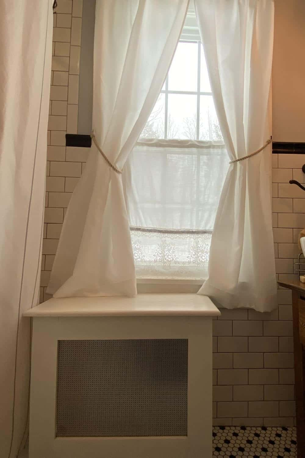 bathroom window with white curtains above radiator