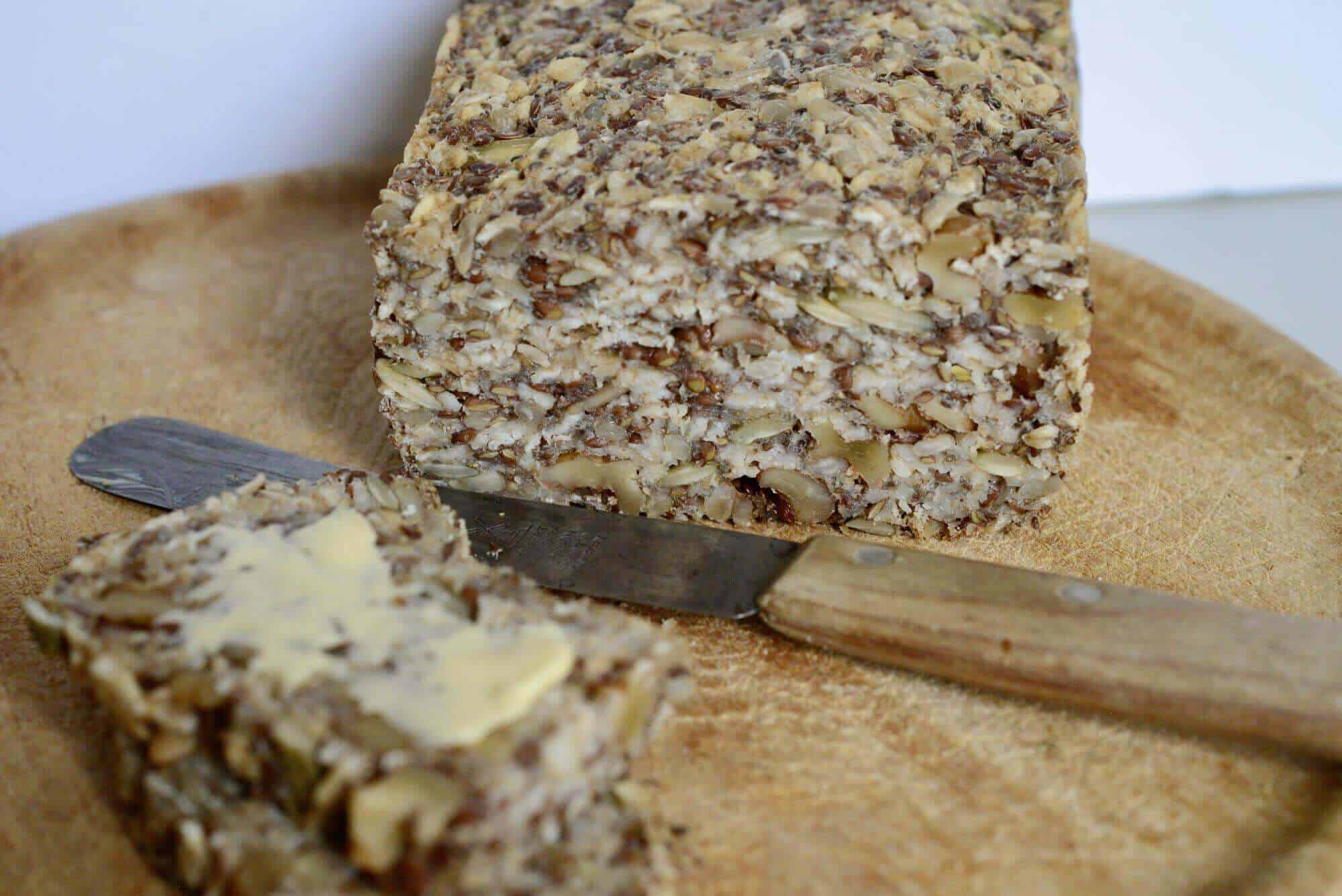 Multigrain bread with knife and butter on board