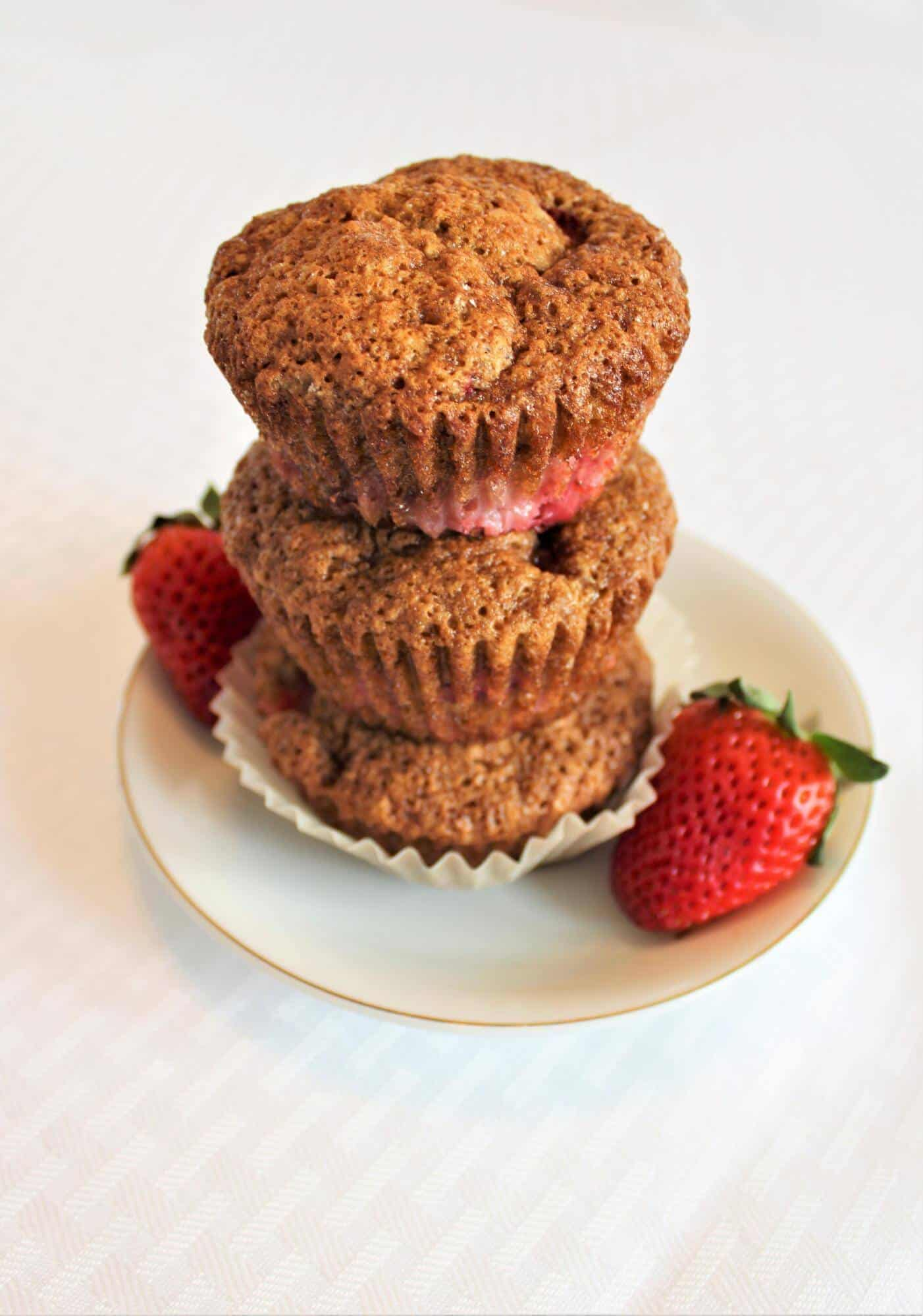 Three muffins and 2 strawberries on plate