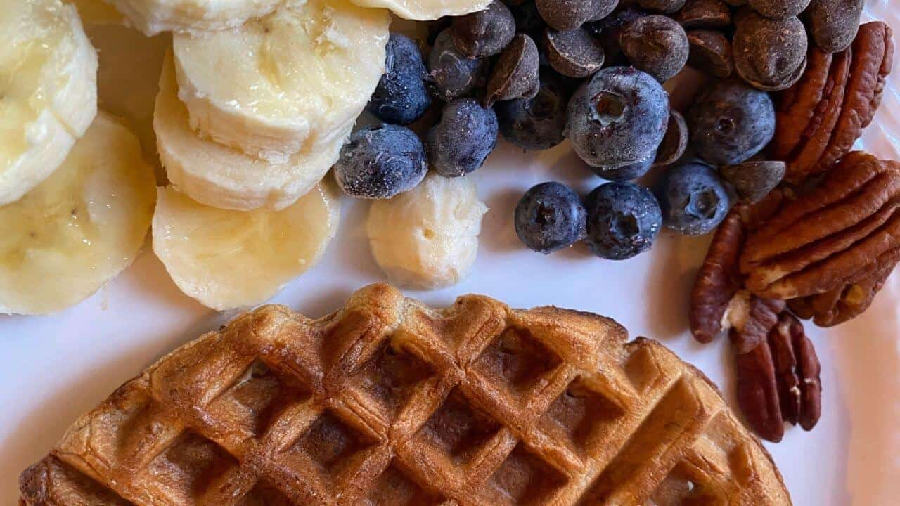 Waffle with banana slices blueberries chocolate chips and pecans