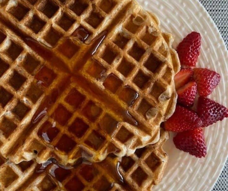 Waffles with syrup and strawberries on white plate